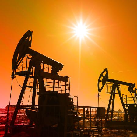 Industrielandschaft Ölpumpen in den frühen Frühling auf einem blauen Himmel Hintergrund