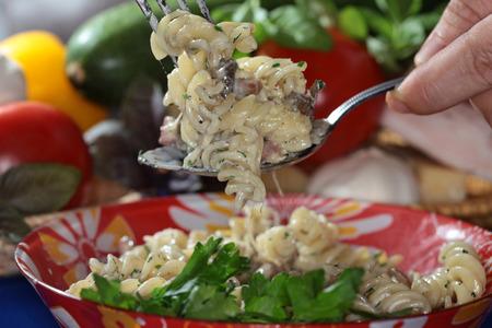 appetizing: macro appetizing Fusilli pasta with cheese on dark background studio Stock Photo