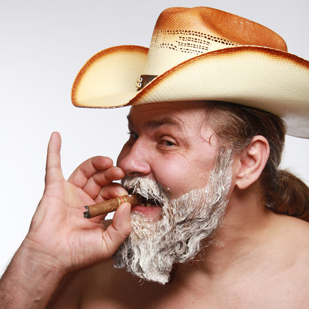 graying: Portrait of a cowboy smoking a cigar at the time of dyeing his beard studio