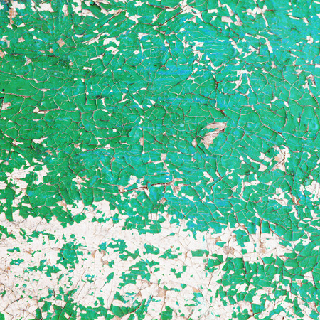 dilapidated wall: macro isolated fragment of the old dilapidated wall painted green-white