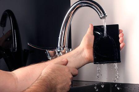 grifo agua: primer plano de tel�fono inteligente bajo el agua del grifo en manos de los hombres