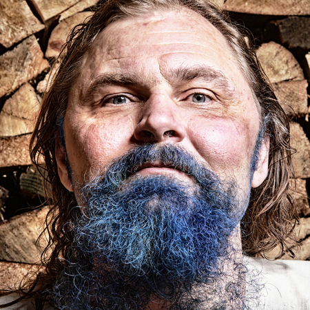 close-up portrait of an adult man with a blue beard and mustache, long blond hair in tissue Cape on background stack of firewood in the bath Standard-Bild