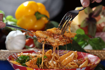 appetizing: macro appetizing Feathers Pasta with cheese and sauce on dark background studio Stock Photo