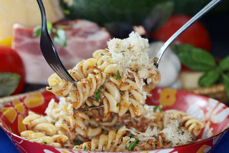 appetizing: macro appetizing Fusilli pasta with cheese and sauce on dark background studio Stock Photo