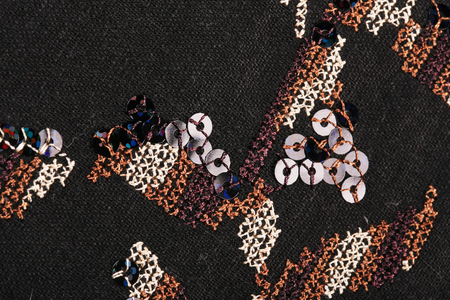 sequins: macro texture brown embroidery thread and sequins on black cloth studio