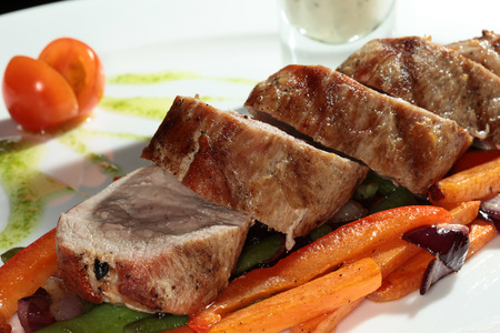 second meal: Close-up of meat with vegetables garnish on a white plate on a black background studio