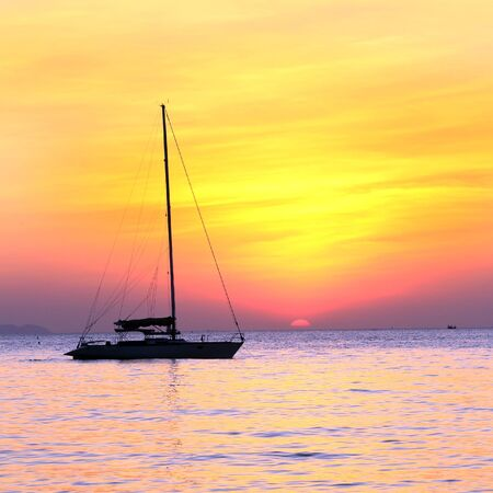 deflated: seascape scenic sunset and anchored boat with deflated sails off the coast of Thailand Stock Photo