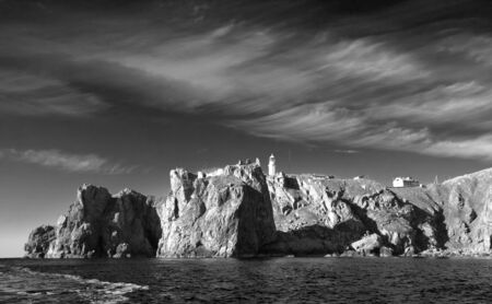 cirrus clouds: Summer seascape lighthouse on the rocky shore and beautiful cirrus clouds in the sky, view from the sea, black-white