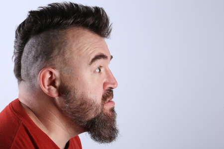 Close-up portrait profile of a white man with mohawk and beard screams in a angry state