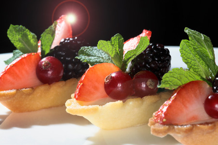 highend: close-up delicious cake with strawberries and blackberries on a dark background Studio