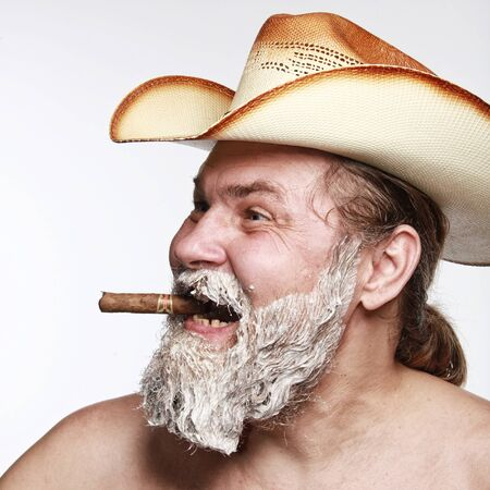 cowboy beard: Portrait of a cowboy smoking a cigar at the time of dyeing his beard studio