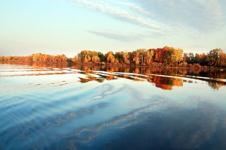 sky blue: autumn landscape beautiful morning on the river, colorful trees on the beach and clouds on blue sky Stock Photo