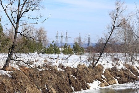 melts: spring landscape melts the ice on the river and power line in spring a bright sunny day