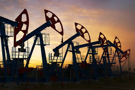 cloud industry: close-up of oil pumps on background of dramatic clouds at sunset