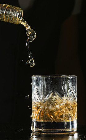An isolated shot of whiskey with a splash on a black background Stok Fotoğraf