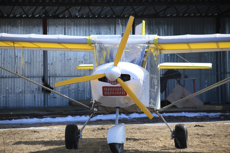 small plane: close-up of a small plane near hangar early spring