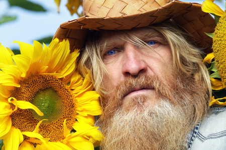portrait of peasant in a field of sunflowers in summer day