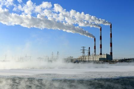 contaminacion aire: humo paisaje invernal de las chimeneas Zainsk TPP contra el cielo azul brumosa mañana escarchada Foto de archivo