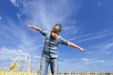close-up eccentric aviator man, arms outstretched in a wheat field against a blue sky