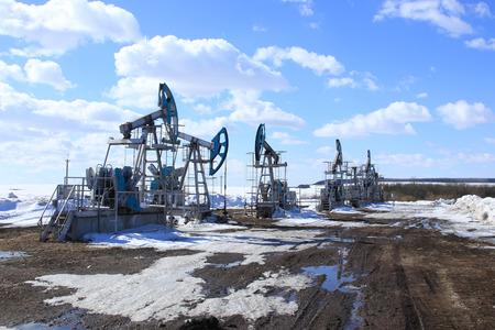 industrieel landschap pompen van de olie in het veld op een achtergrond van blauwe hemel en witte wolken op een zonnige dag in de vroege lente