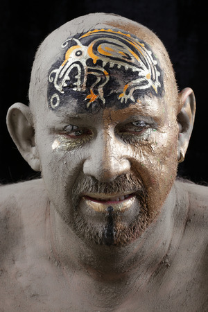 black moor: close-up bald man in a clay with ethnic pattern on the forehead on a black background Studio Stock Photo