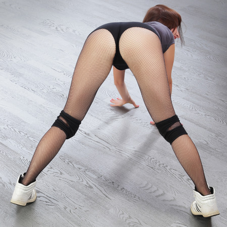 pant: close-up sexy redhead girl showing sports buttocks on a background of gray flooring studio