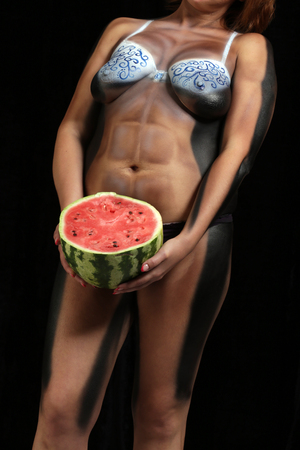 body painting: close-up of a womans body painting, athletic body with watermelon in hands on a black background Studio