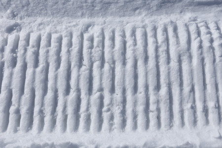 mechanization: macro texture tractor tracks in the snow on a sunny day Stock Photo