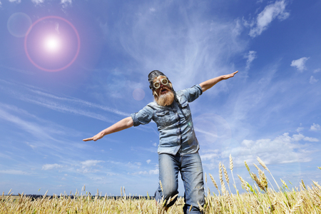 steampunk goggles: close-up eccentric aviator man, arms outstretched in a wheat field against a blue sky