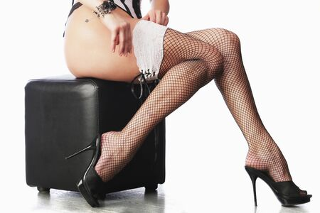 pouf: seductive woman in lingerie and stockings sitting on pouf on white background studio