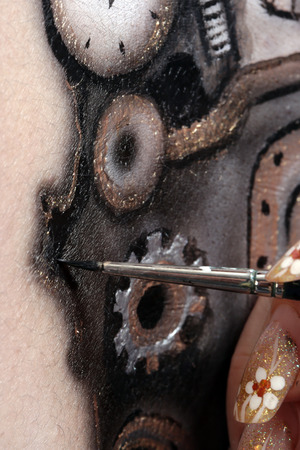 body painting: close-up of a womans body painting, marionette doll with a mechanism on a black background Studio Stock Photo