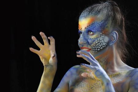 close-up of body art - the girl chameleon on a dark background Studio
