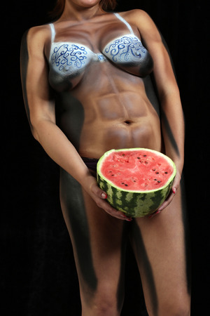athletic body: close-up of a womans body painting, athletic body with watermelon in hands on a black background Studio