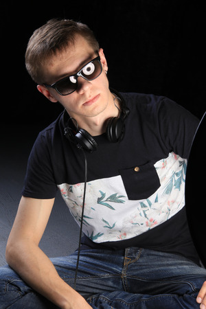 close-up portrait of a young man DJ with headphones on dark background studio