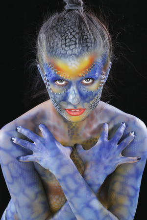 close-up of body art - the girl chameleon on a dark background Studio Stockfoto - 97234324