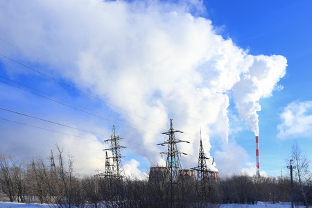 close up chimney: industrial landscape smoke from the chimneys large plant and power lines against the blue sky in winter Stock Photo