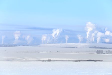 snowcovered: panorama of snow-covered fields and smoke from the chimneys of the plant on the horizon frosty misty morning