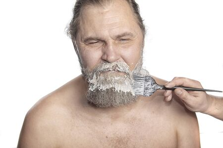 graying: Portrait of a charismatic adult man at the time of dyeing his beard studio Stock Photo