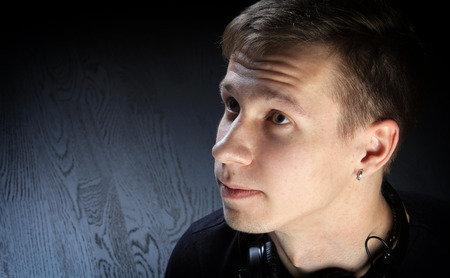 close-up portrait of a young man DJ with headphones on dark background studio Stockfoto - 97234104