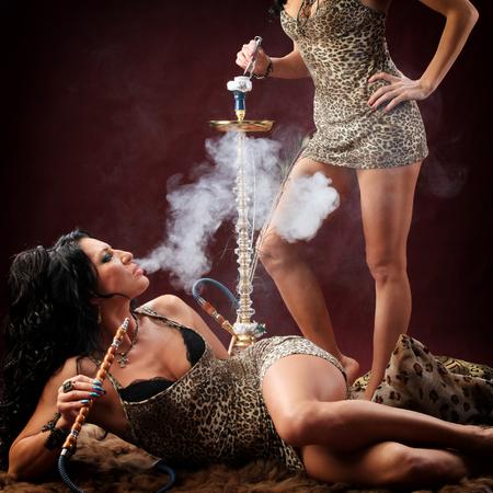 sexy girl dance: portrait of oriental girls on burgundy background in the studio smoke hookah and dance