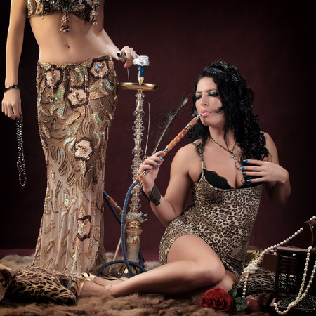 portrait of oriental girls on burgundy background in the studio smoke hookah and dance