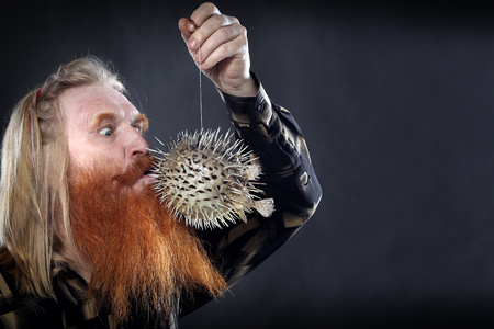 Portrait of an adult man with a red beard and mustache with the globefish on a dark background studio Stock Photo