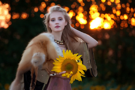 closeup portrait of a young beautiful girl with long blond hair in a beautiful dress in antique style on a background field of sunflowers at sunset