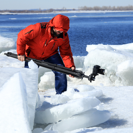 photographer takes the ice on the river in a flood in early spring on a sunny day