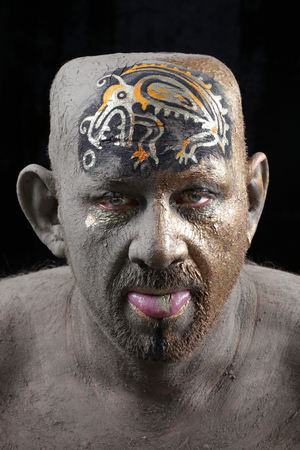 close-up portrait of a man in the clay body art, studio on a dark background
