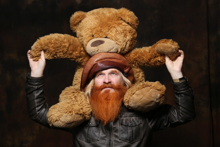 Portrait of an adult man with a red beard and mustache with a teddy bear on a dark background studio