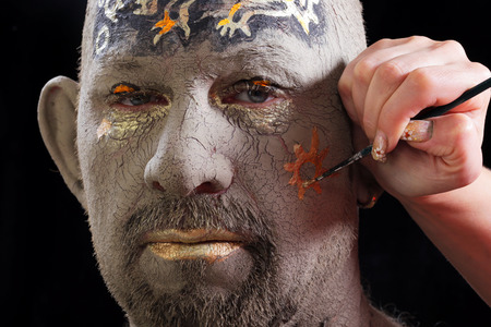 craquelure: close-up portrait of a man in the clay body art , studio on a dark background