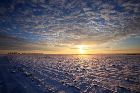 covered fields: winter landscape snow-covered fields and roads in sunlight rays on the sunset