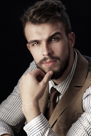 closeup portrait of the beautiful charismatic young man with a beard wearing pants, shirt, vest and tie on a dark background studio