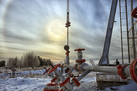 closeup of an oil pump in a snowy field near a forest in the sunlight halo